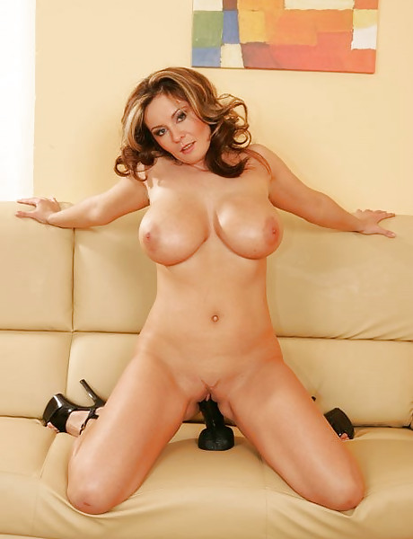 Busty MILF lady takes her black thongs off on the sofa and masturbates in black heels