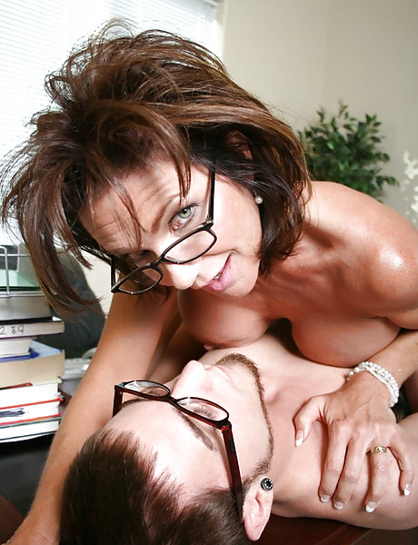 Horny MILF babe strips in the office and gets fucked by her younger horny coworker.