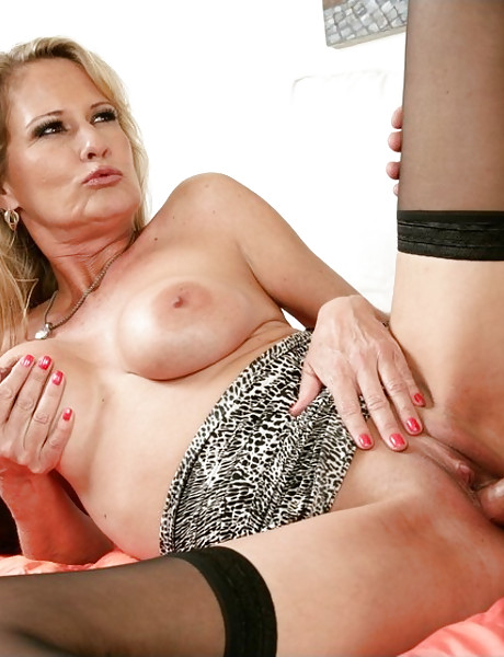 Classy blonde MILF takes her dress off and fucks in black stockings and lingerie.