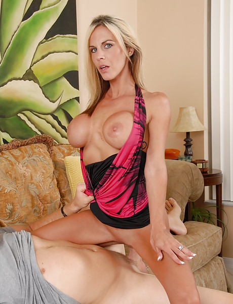 Big breasted blonde babe takes her black dress on the sofa and blows a cock.