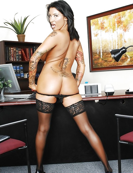 Classy tattooed brunette babe strips in the office and gets fucked in stockings.