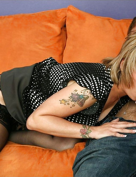 Hot busty blonde MILF takes her clothes off on the sofa and slurps on hard boner.