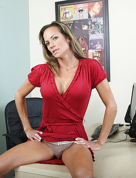 Tanned brunette secretary with sexy hooters wearing red dress playing with her cunt