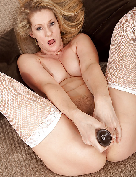 Horny blonde momma wearing white thong and fishnet stockings playing with a dildo
