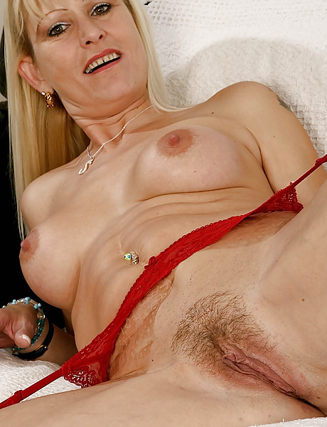 Sexy blonde milf in hot red lace lingerie stripping and teasing with her hairy pussy