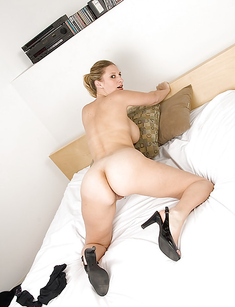 Hot blonde with big saggy boobs and a soft shaved pierced pussy poses on bed