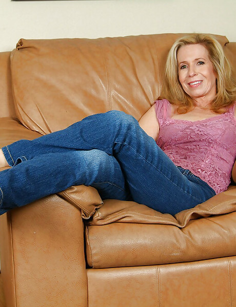 Horny blonde granny gets naked on a leather sofa and shows her wet hairy pussy