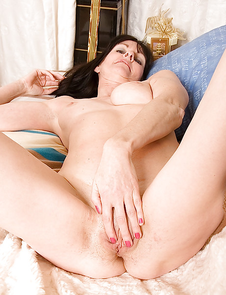 Hot skinny brunette mature babe gets naked and fingers her wet pussy on a couch