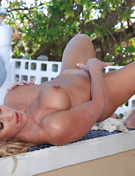 Hot tanned blond bombshell fingering her tight sweet pussy putside by the pool