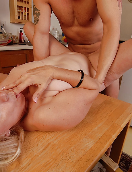 Sexy curvy busty milf has hot sex on the kitchen table with a young strong stud