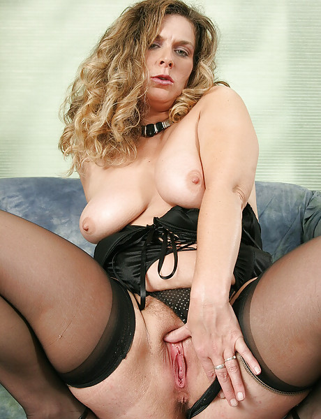Sexy blond babe drops down her cute black corset and masturbates with her dildo