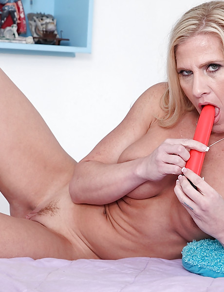 Beautiful blond model gets rid of her sexy clothes and masturbates with a red dildo