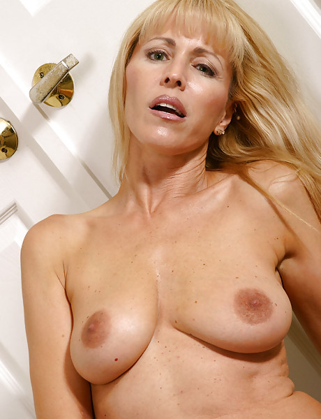 Hot and sexy blond MILF gets rid of her blue shirt and shows her tits and her twat