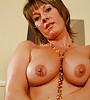 Sexy milf with a tight tanned body and saggy boobs gets naked on a black leather sofa