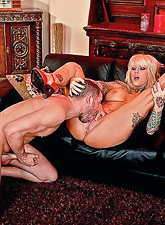 Big breasted tattooed bitch kneels before her hung lover and sucks his big shaft