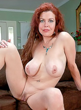 Big breasted redhead lady takes her lingerie off and shows her big round melons.