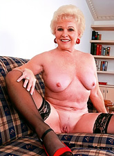 Horny classy blonde granny takes her clothes off and fucks in black stockings.