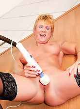 Nasty tanned blonde momma wearing black g-string playing with a vibrating sex toy