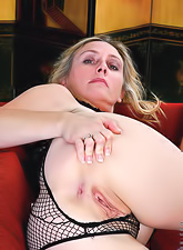Horny blonde in sexy black fishnets fngering her tasty shaved pussy and teasing