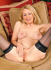 Hot blonde milf in sexy black naylon stockings stripping and fingering her pussy