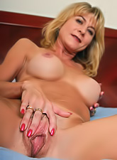Hot blonde milf stripping and showing her big round boobs and wet shaved pussy