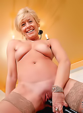 Horny granny in sexy tight dress stripping and masturbating with big black dildo