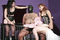 Vinyl Queen and two kinky, slutty bitches play with oen submisssive, horny male sex slave