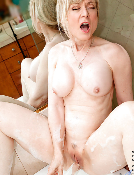 Busty classy blonde lady takes her lingerie off and then showers her big jugs