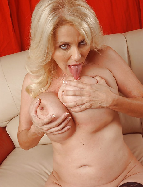 Busty blonde MILF lady takes her dress off and shows us her massive big jugs.