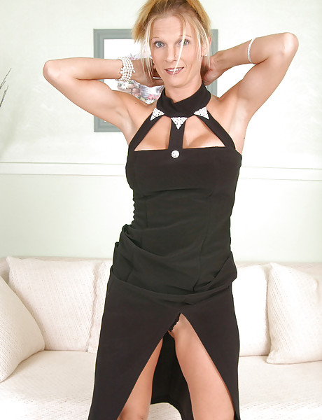 Sexy blonde in a sexy black dress stripping and showing her shaved wet pussy
