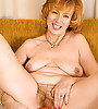 Hot MILF babe gets naked on her couch and masturbates with her orange dildo