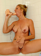 Seductive blonde MILF lady strips under the shower and toys her hungry vagina