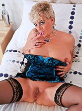 Classy blonde granny teases us on the bed in sexy black stockings and blue lingerie