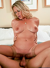 Big breasted classy MILF seduces younger dude and fucks his big cock on the bed.