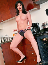Attractive brunette vixen takes her black lingerie off and fucks in the kitchen.