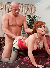 Classy redhead MILF babe takes her red lingerie off and fucks in stockings.