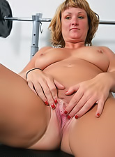 Horny young milf getting horny in the gym, stripping and fingering her pussy