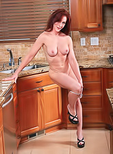 Sexy busty ginger milf with a hot slim body stripping and teasing in the kitchen