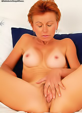 Sexy redhead mature slut with tight round boobs fingering her wet shaved pussy