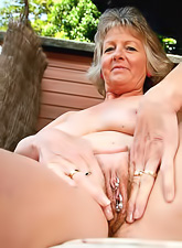Slutty granny in a sweet summer dress strips and shows her meaty hairy pierced cunt