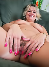 Cute and horny housewife gets naked on her couch and shows her tits and pussy