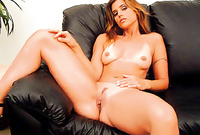 Cherie spreads her sexy legs on the black sofa and passionately fingers her fully shaved hungry vagina