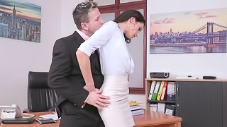 A babe is with her boss in the office and she is spreading her legs for him